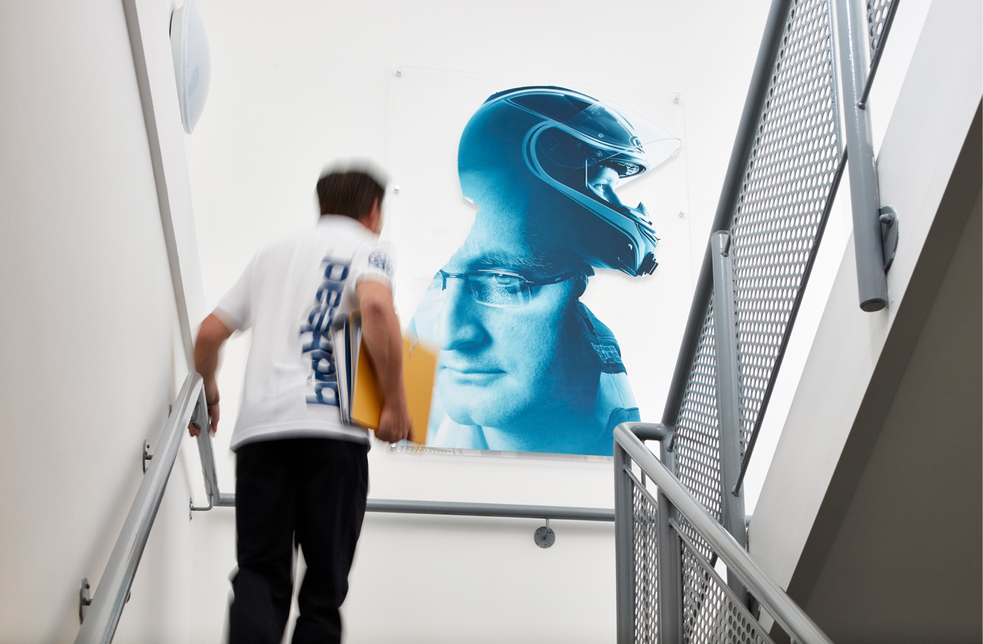 interior graphics on wall as man walks up staircase